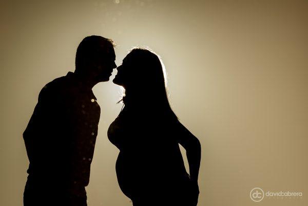 Foto de embarazo pareja en silueta besándose. Por David Cabrera Fotografía