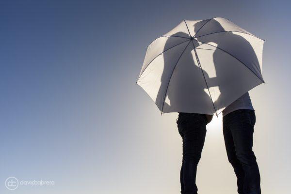 Foto de embarazo pareja en silueta con paraguas. Por David Cabrera Fotografía