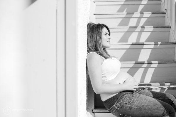 Foto de embarazo sentada en escalera. Por David Cabrera Fotografía