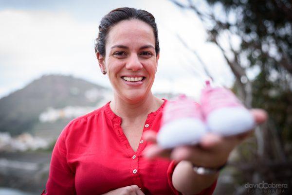 Foto embarazo. Madre mostrando zapatos de bebé. Por David Cabrera Guillén